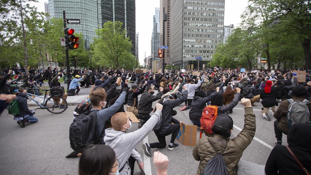 Des manifestants mettent un genou au sol et lèvent le poing à la place du Canada au centre-ville de Montréal.