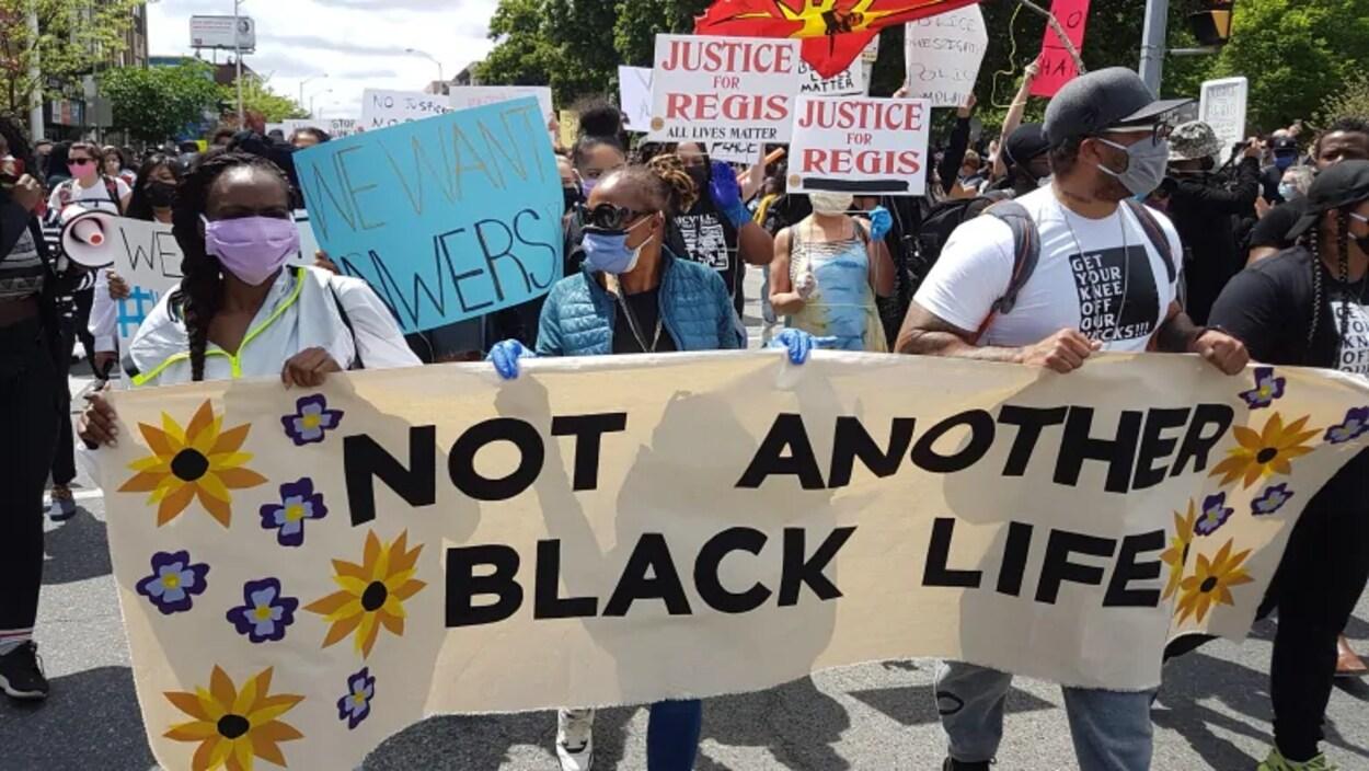 Les manifestants tiennent une banderole portant le message «pas une autre vie d'un Noir perdue ».
