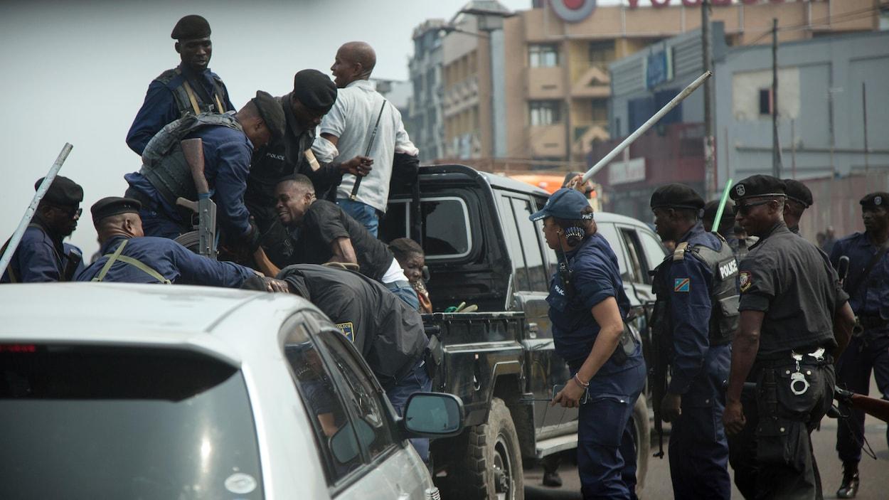 Un manifestant est tiré à l'arrière d'une camionnette de la police sous la menace de recevoir un coup de bâton.