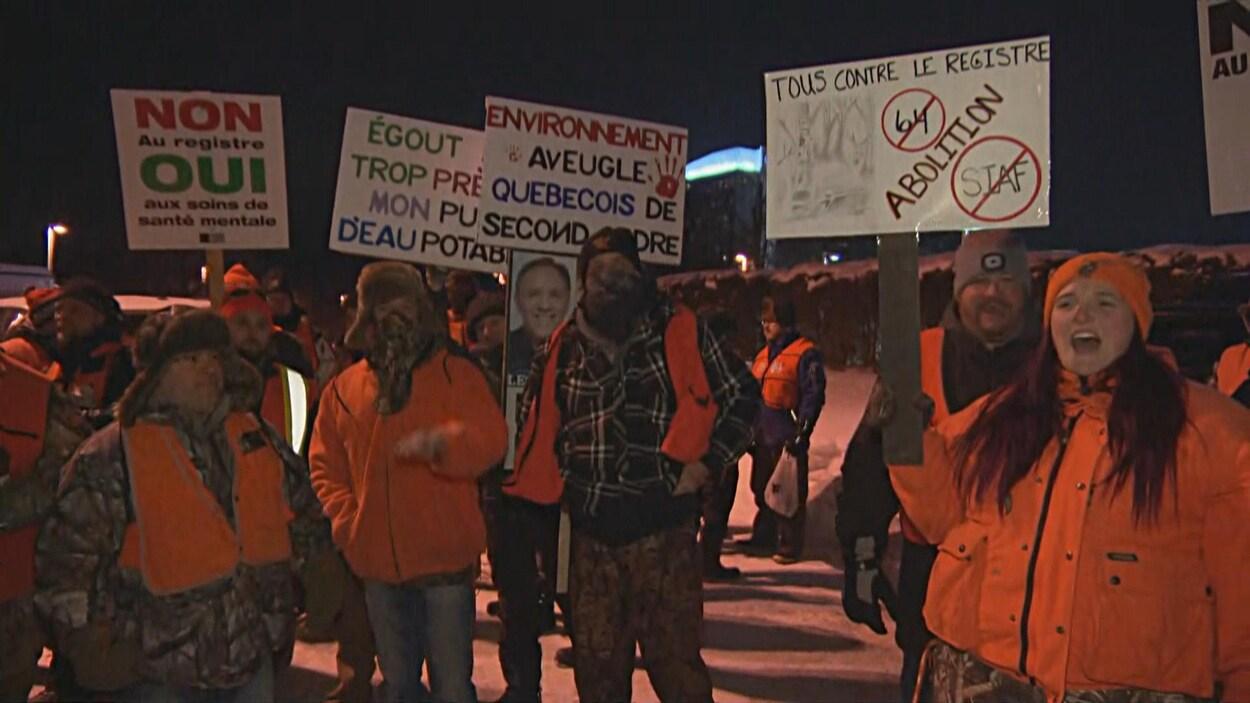 Des manifestants tiennent des affiches sur lesqelles on peut lire « Tous contre le registre » et « Non au registre. Oui aux soins de santé mentale ».