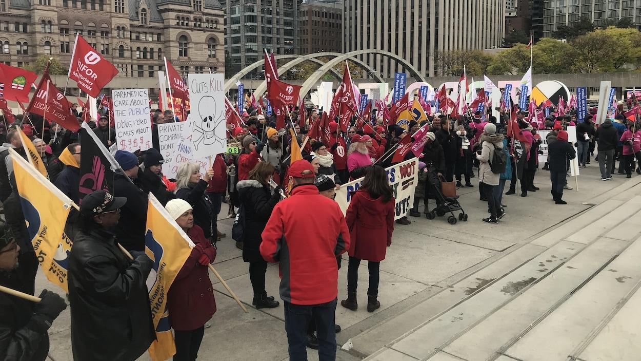 Des centaines de manifestations avec des t-shirts rouge sur une place du centre-ville de Toronto.
