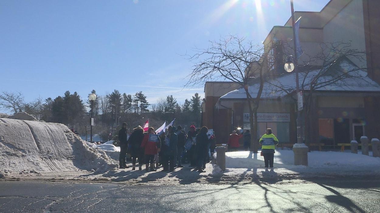 Quelques dizaines de manifestants, drapeaux et pancartes à la main, devant les bureaux de la député Marie-France Lalonde.