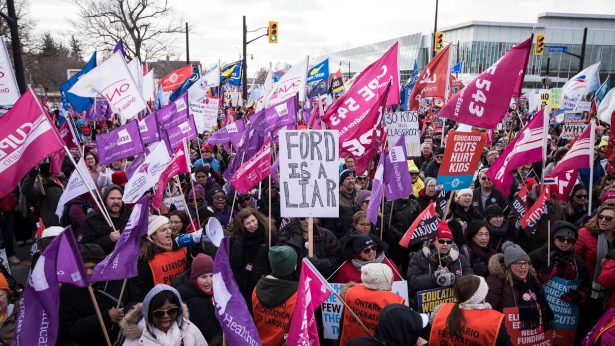 Des centaines de personnes qui tiennent des pancartes et drapeaux.