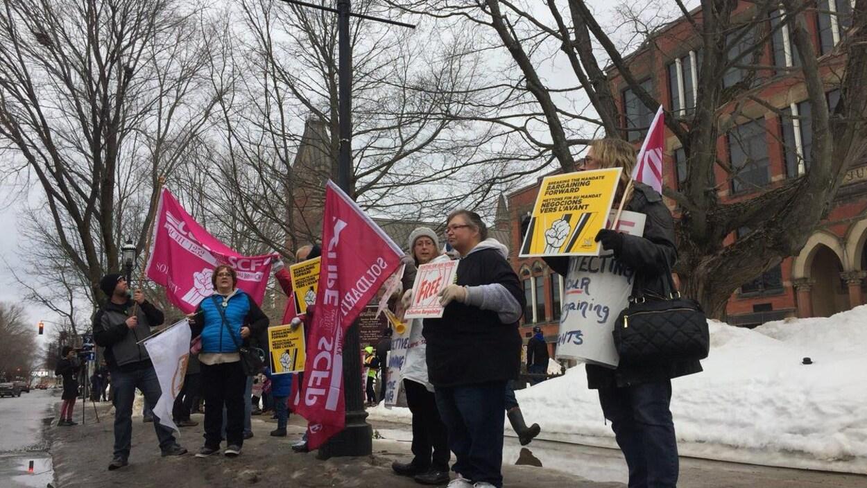 Des syndiqués qui brandissent pancartes et banderoles au centre-ville de Fredericton.