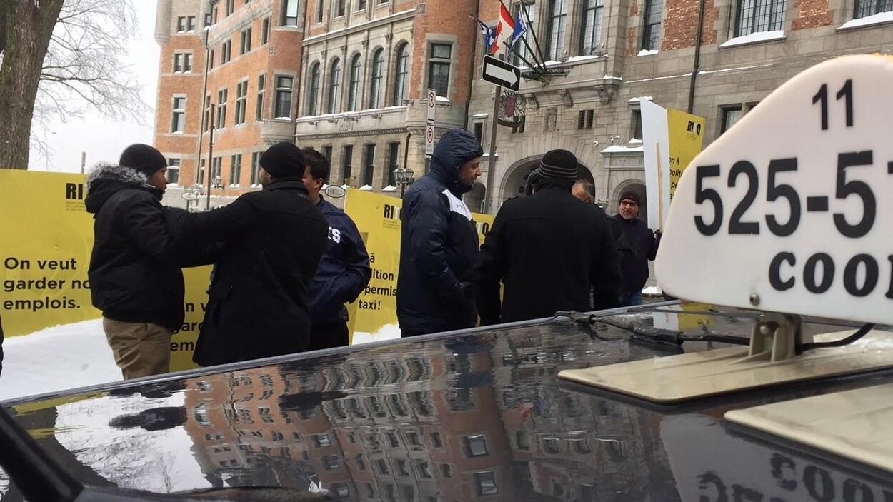 Des chauffeurs de taxis avec des pancartes regroupés devant le château Frontenac.