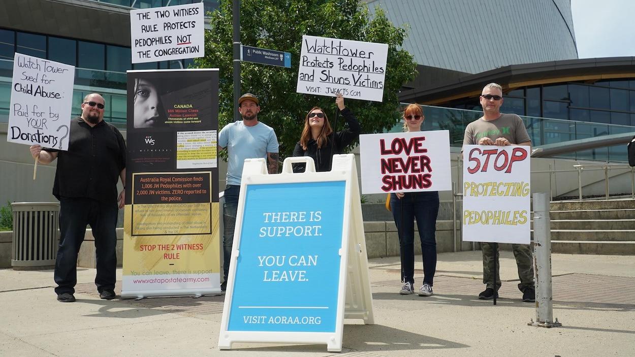 5 personnes munies de pancartes