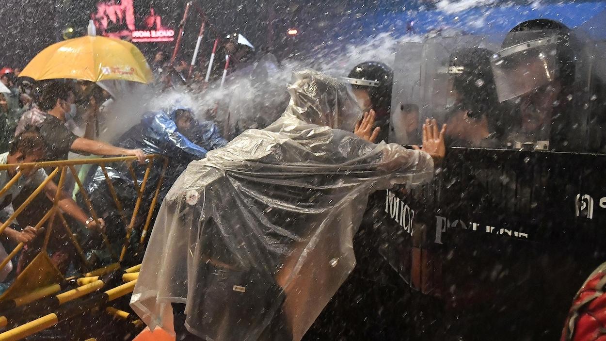 Des manifestants et policiers s'affrontent sous les jets d,eau.