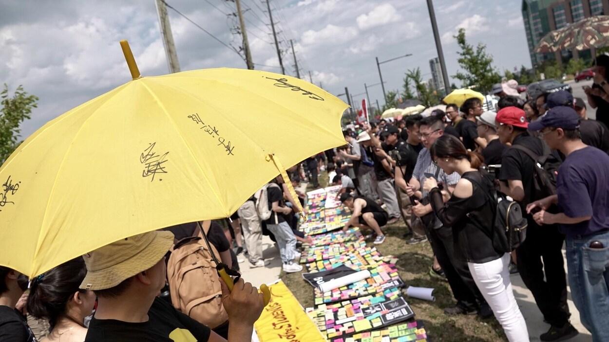 Des personnes sont rassemblées devant des affiches posées au sol où des mots sont déposés sur des post-it, et un homme au premier plan porte un parapluie jaune.