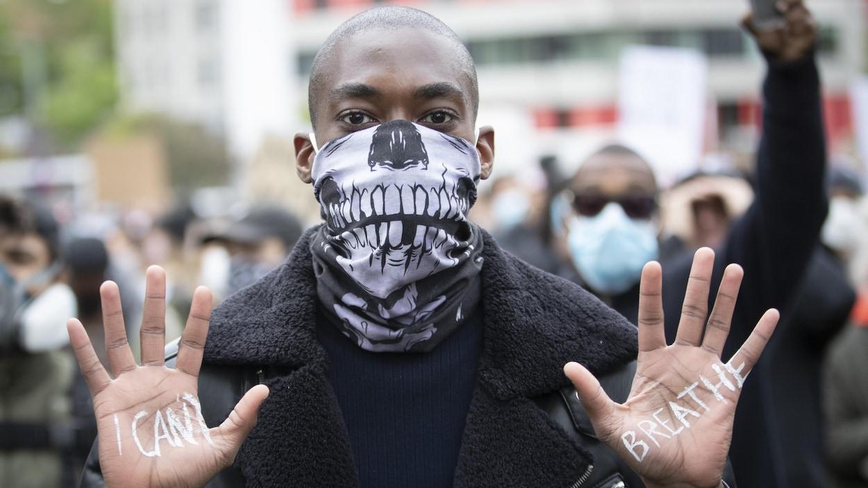 Un homme noir montre les paumes de ses mains où il est écrit « Je ne peux pas respirer ».