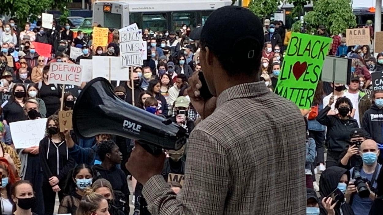 Un homme fait un discours devant des centaines de manifestants réunis devant le Musée des beaux-arts de Vancouver.