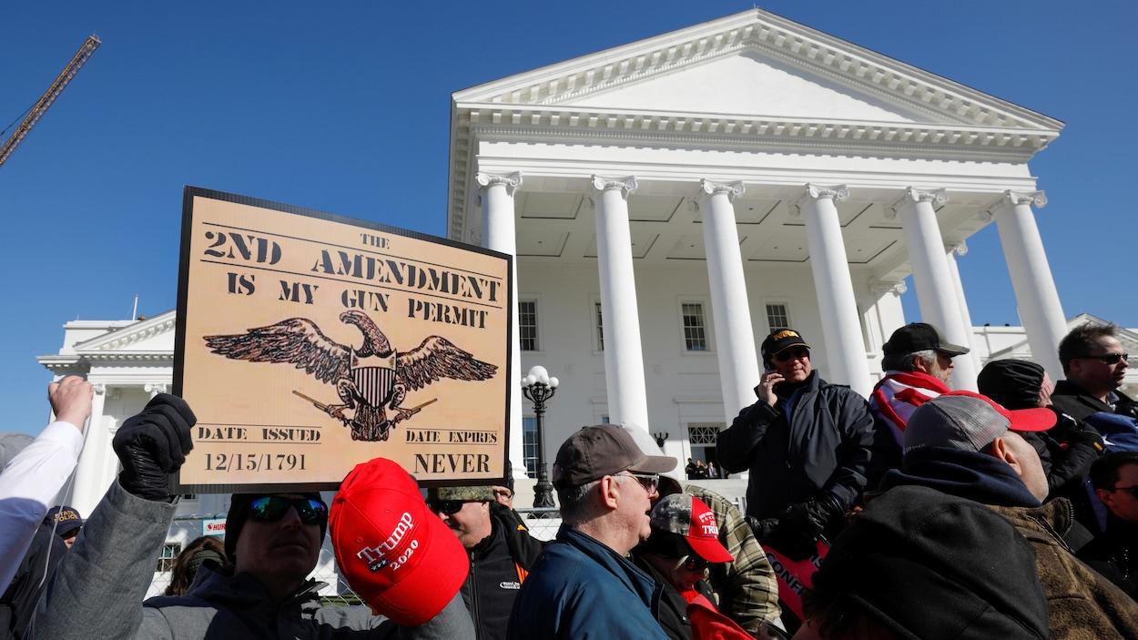 Le 20 janvier 2020, un militant proarmes tient une casquette appuyant Donald Trump et une pancarte disant « Le deuxième amendement est mon permis d'armes à feu ». Il se trouve devant le capitole de l'État de Virginie.