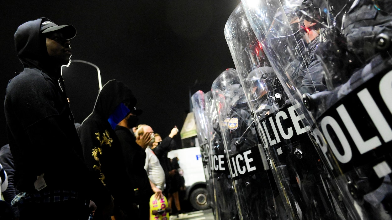 Des manifestants sont alignés devant des policier de l'escouade antiémeute.