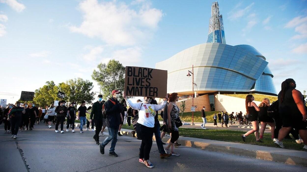 Des personnes marchent dans une rue en tenant des affiches, devant le Musée canadien pour les droits de la personne.