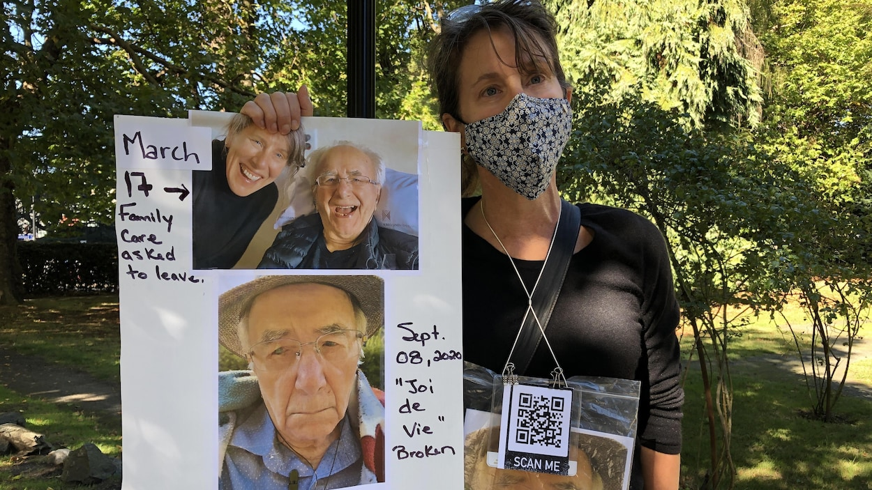 Hélène Michaud tenant dans ses mains une affiche avec des photos de son père.