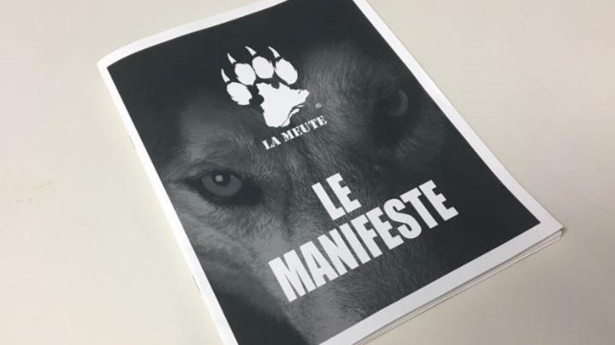 Copie du manifeste de La Meute. La couverture du document montre une tête de loup ainsi que le logo de La Meute : une empreinte de patte de loup à quatre doigts dont la paume est formée par une représentation géographique du territoire du Québec et du Labrador.
