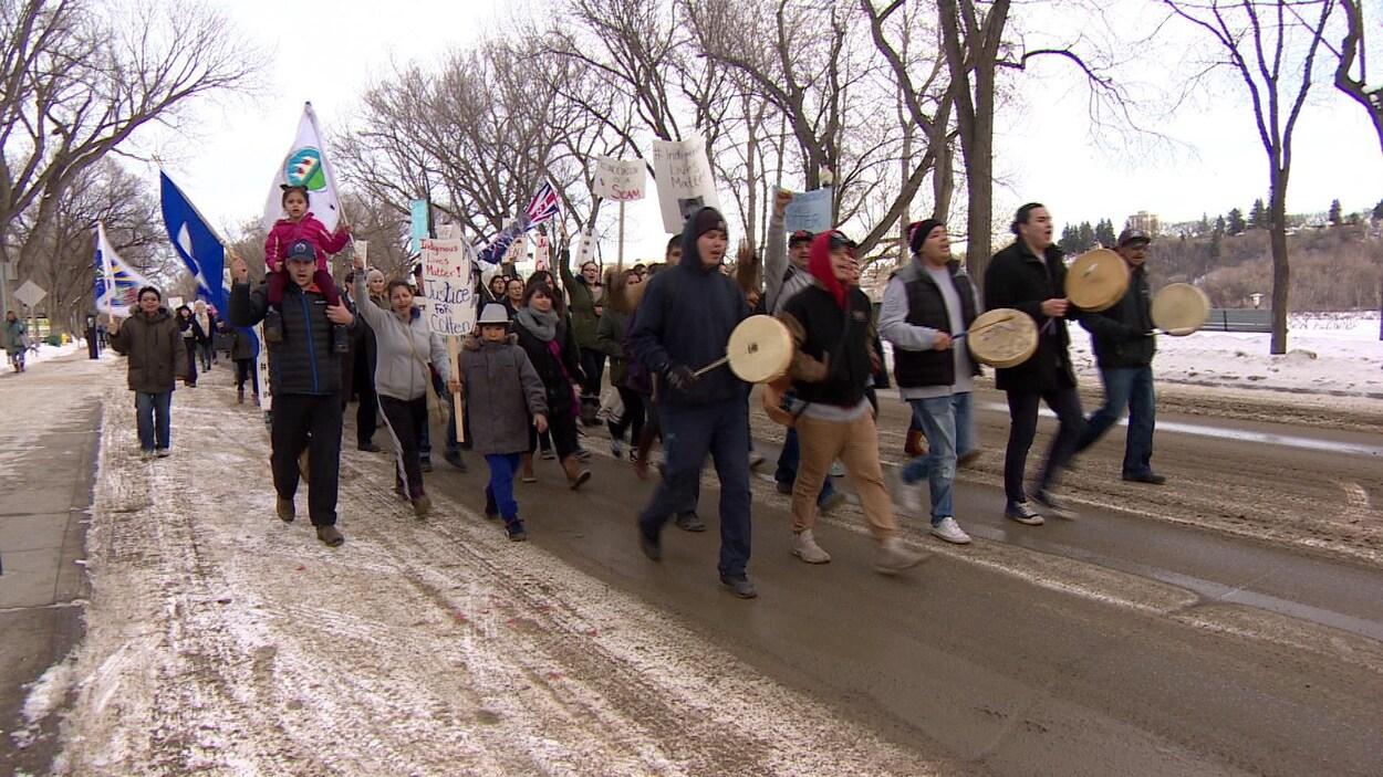 Des gens marchent dans la rue avec des tambours.