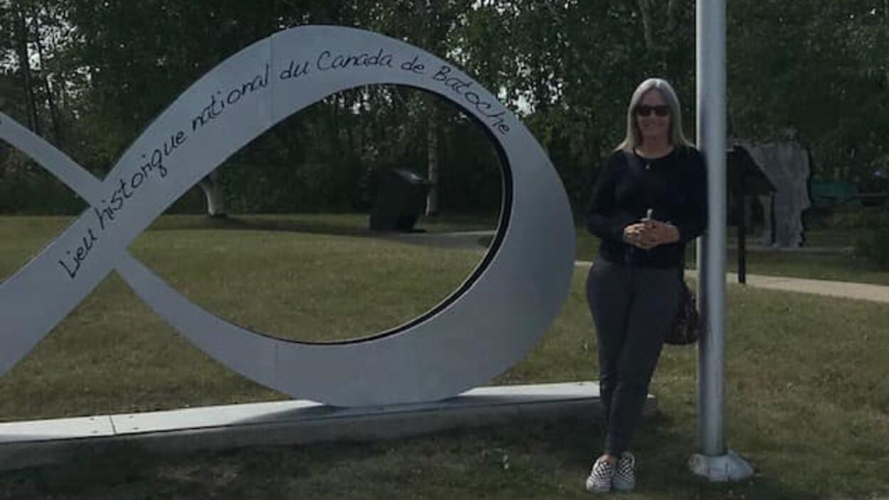 Mona Kines à coté d'une enseigne à Batoche.