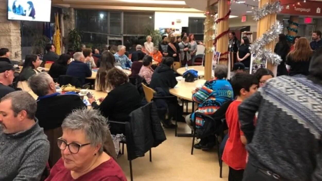 Un groupe de personnes dans une salle décorée autour de plusieurs tables.