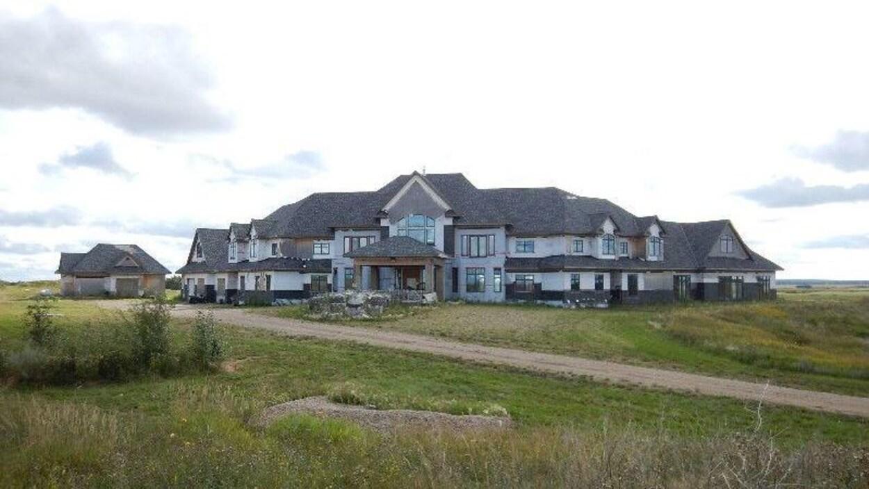 Un grand manoir de deux étages au bout d'une route de terre et entouré de prairies.