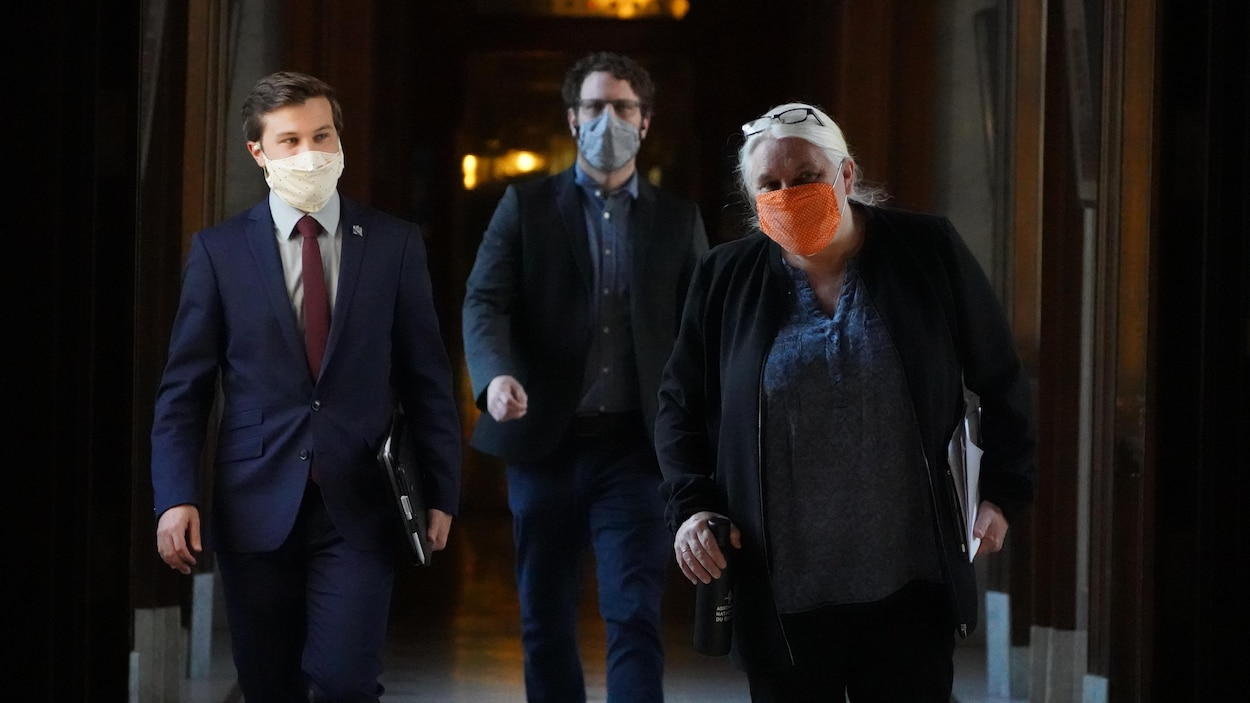 Manon Massé et Gabriel Nadeau-Dubois, suivis d'un homme non identifié, marchent et portent un masque.