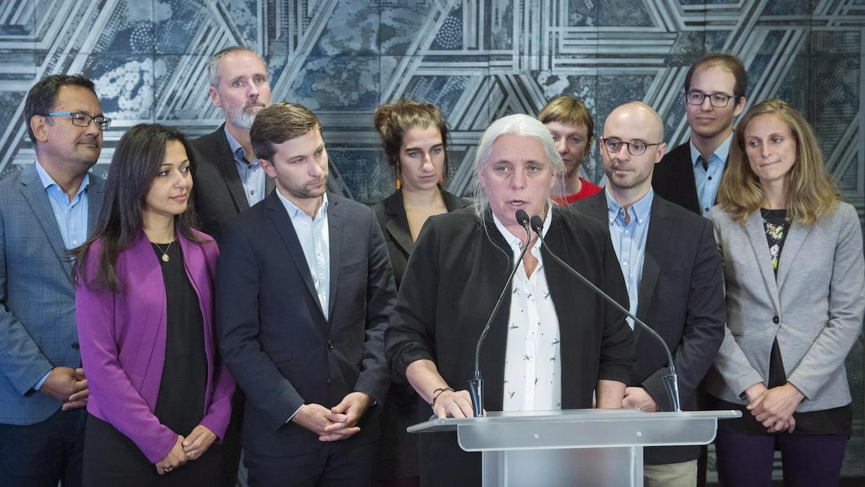 Manon Massé parle en conférence de presse, tous les députés élus de QS se tiennent derrière elle.