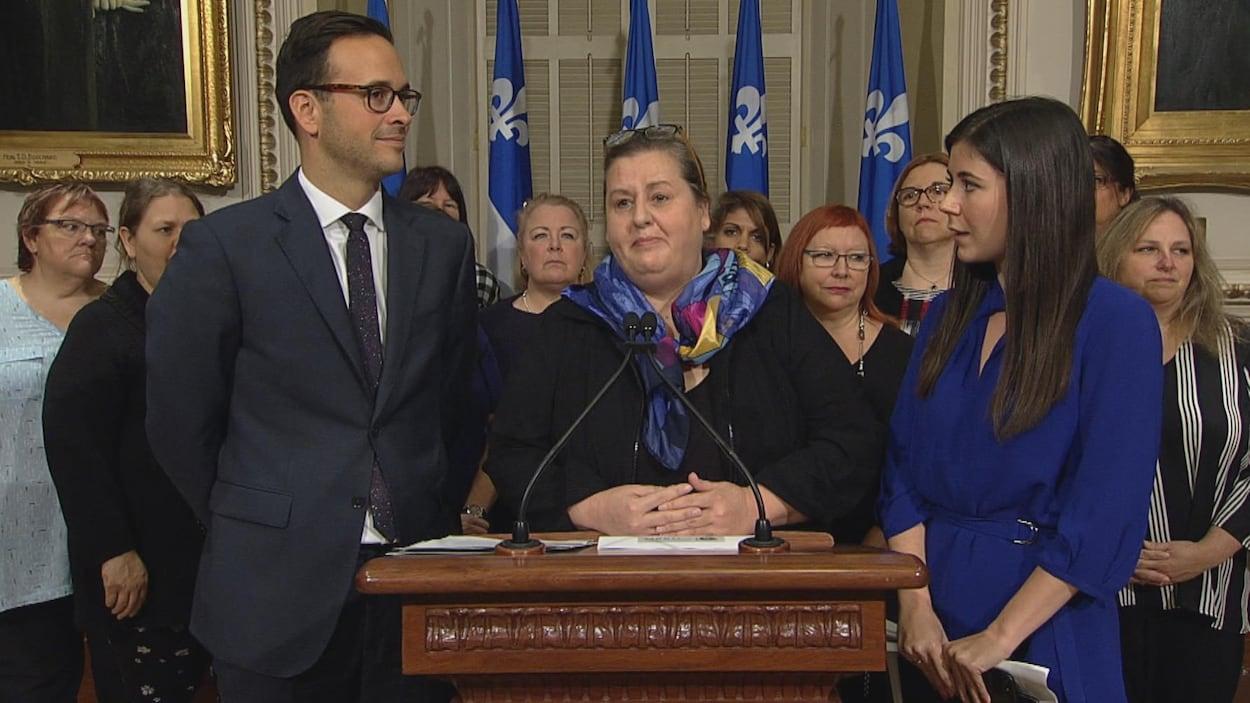 La directrice de la Fédération des maisons d'hébergement pour femmes du Québec, Manon Monastesse, entourée des députés péquistes Alexandre Cloutier et Catherine Fournier.
