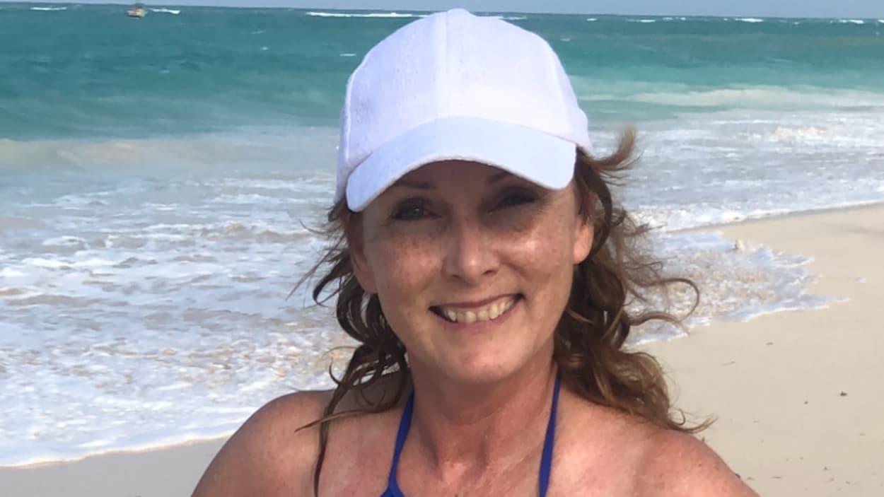 Une femme debout sur le bord de la mer.