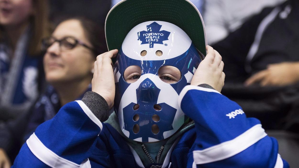 Un jeune partisan des Maple Leafs qui porte un masque aux couleurs de l'équipe.