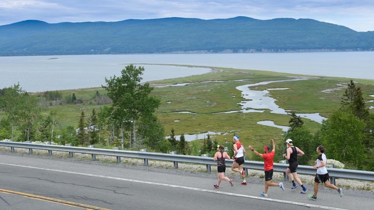 Des coureurs sur une route devant la baie de Gaspé.