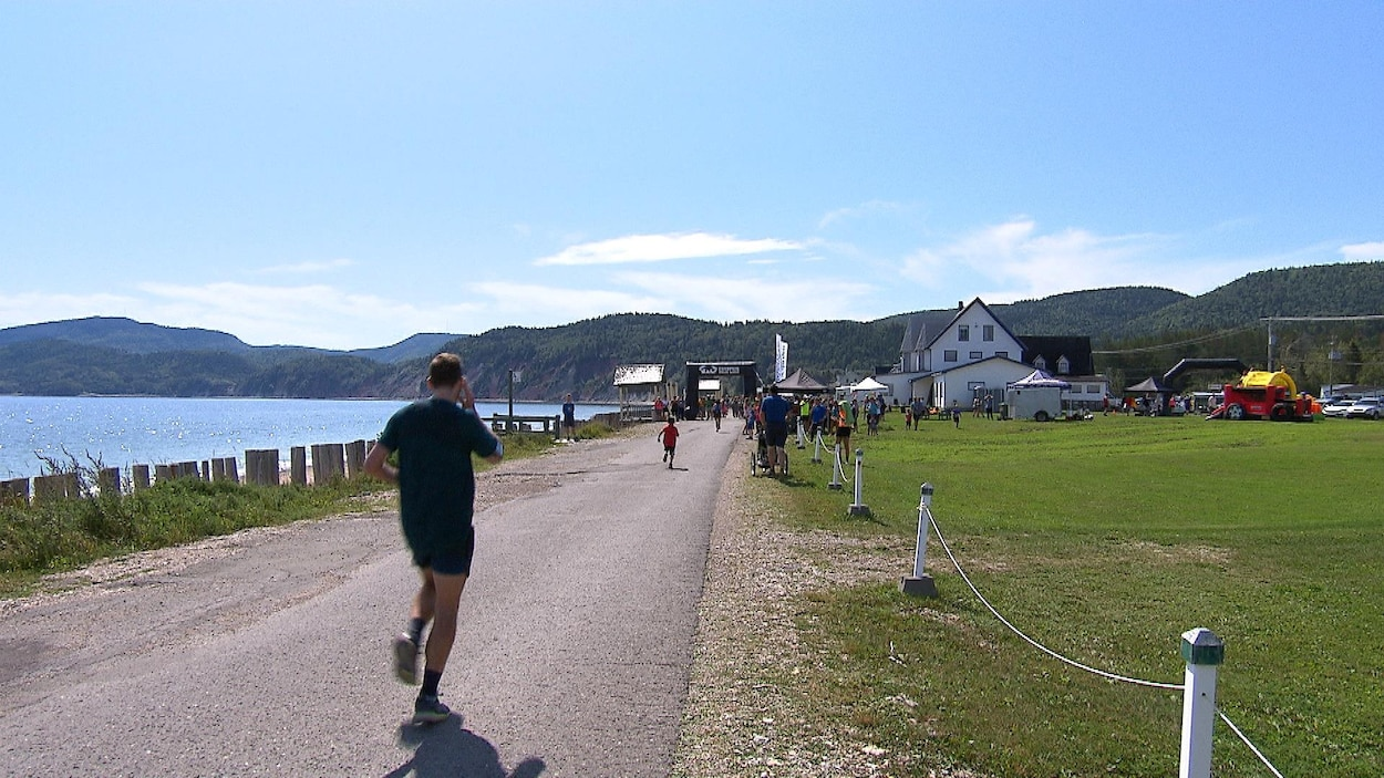 Des coureurs arrivent à la fin de leur course, sur paysage du Coin-du-Ban avec ciel bleu, petites montagnes et eau scintillante