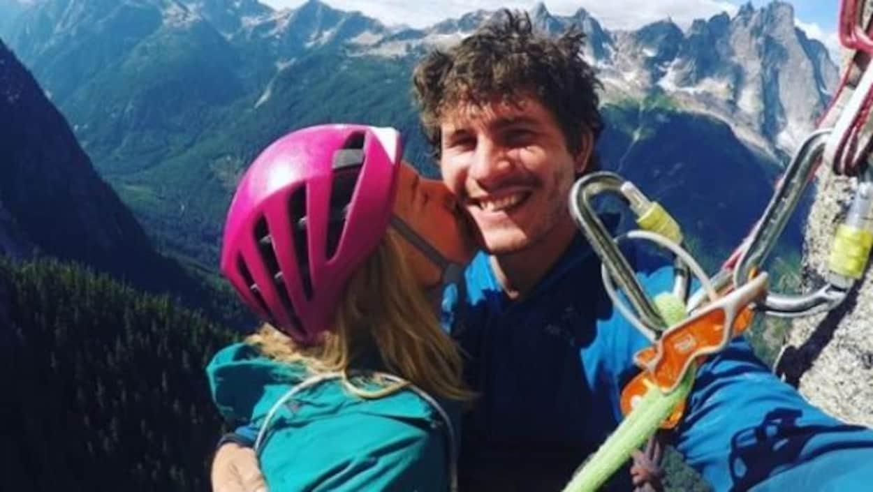 Une jeune femme blonde embrasse un jeune homme aux cheveux bruns frisés sur la joue. Ils sont au sommet d'une montagne.