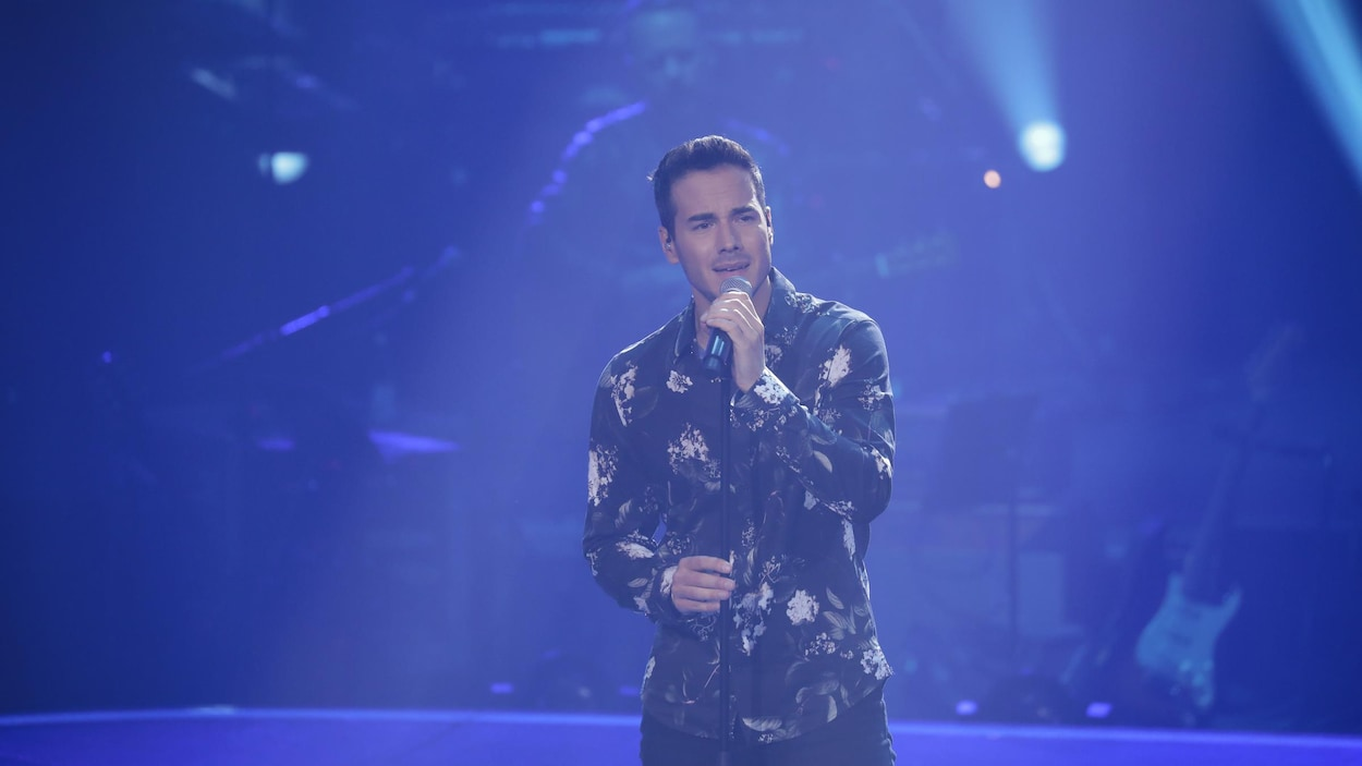 Un homme chantant sur scène.