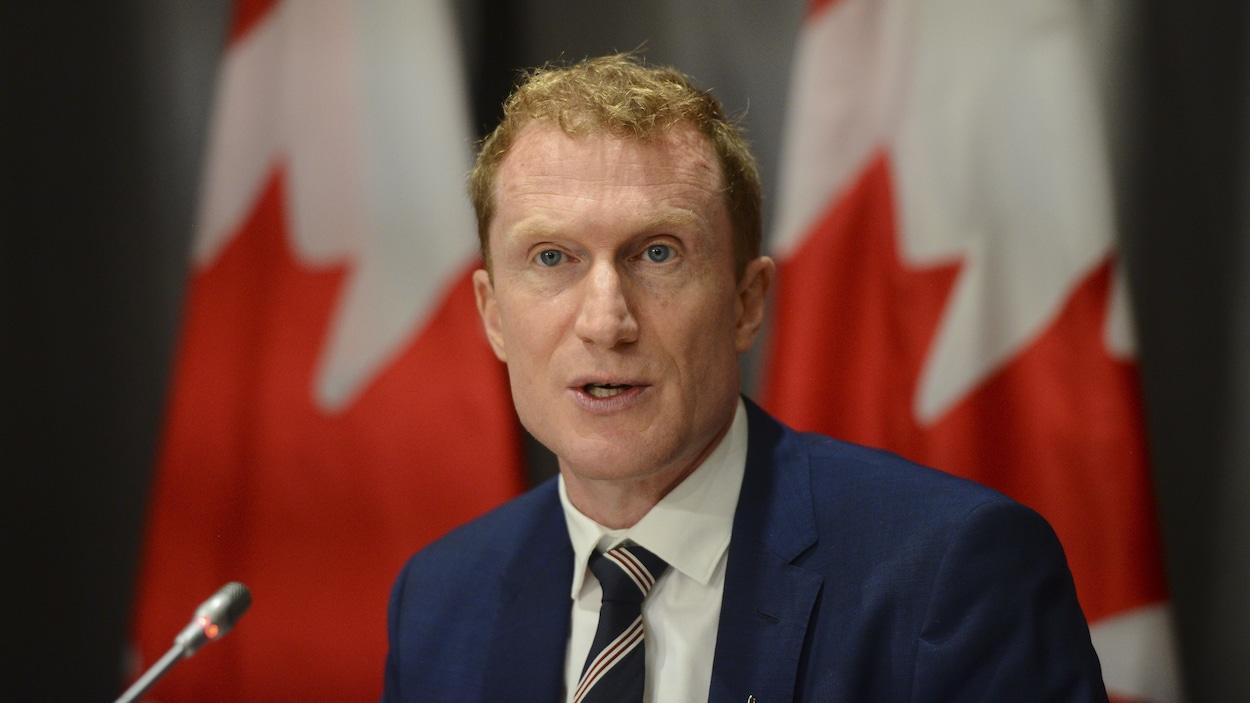 Marc Miller en conférence de presse devant deux drapeaux du Canada.