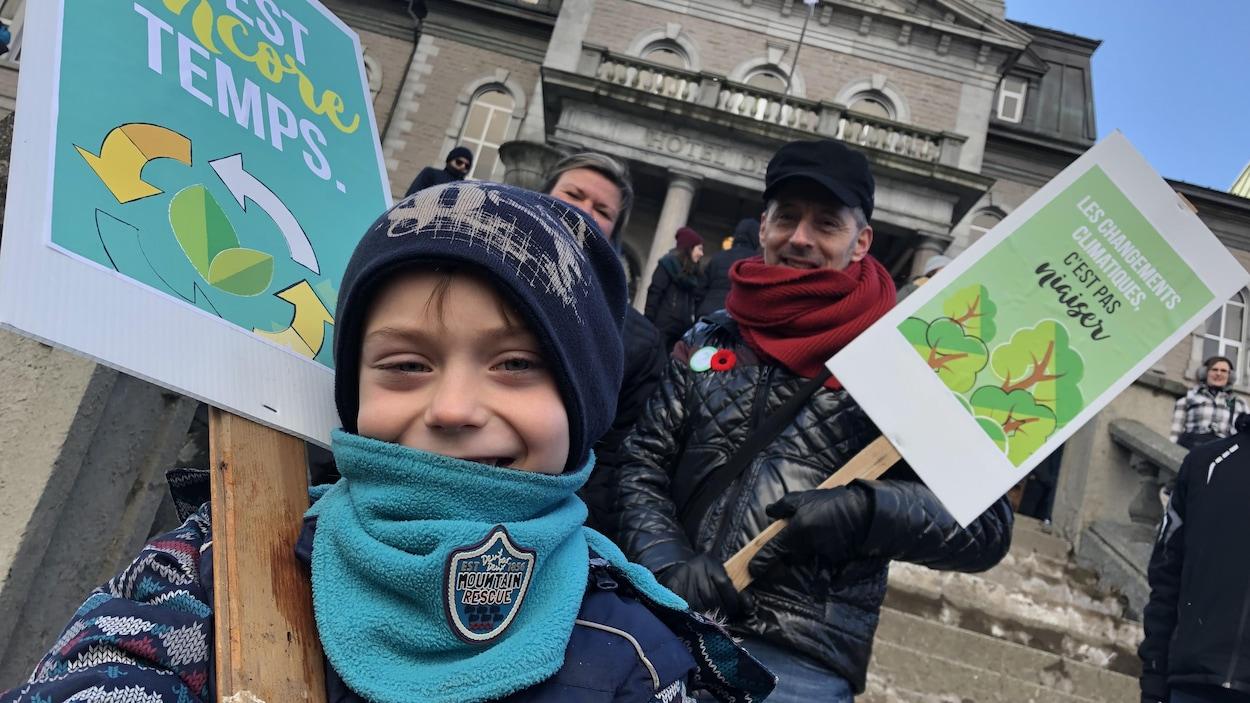 Un enfant et un homme tiennent des pancartes.