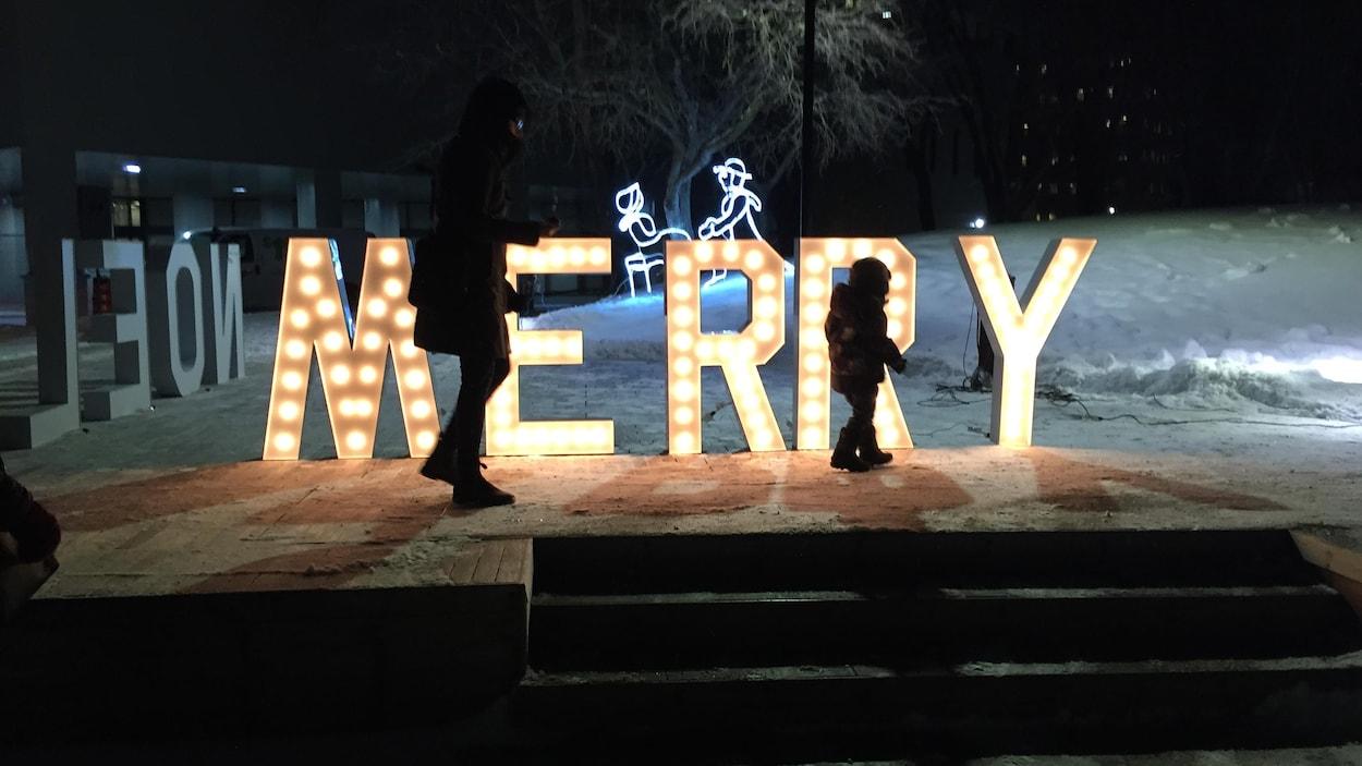 Une mère et son jeune enfant marchent devant un grand signe illuminé lisant Merry sur une scène