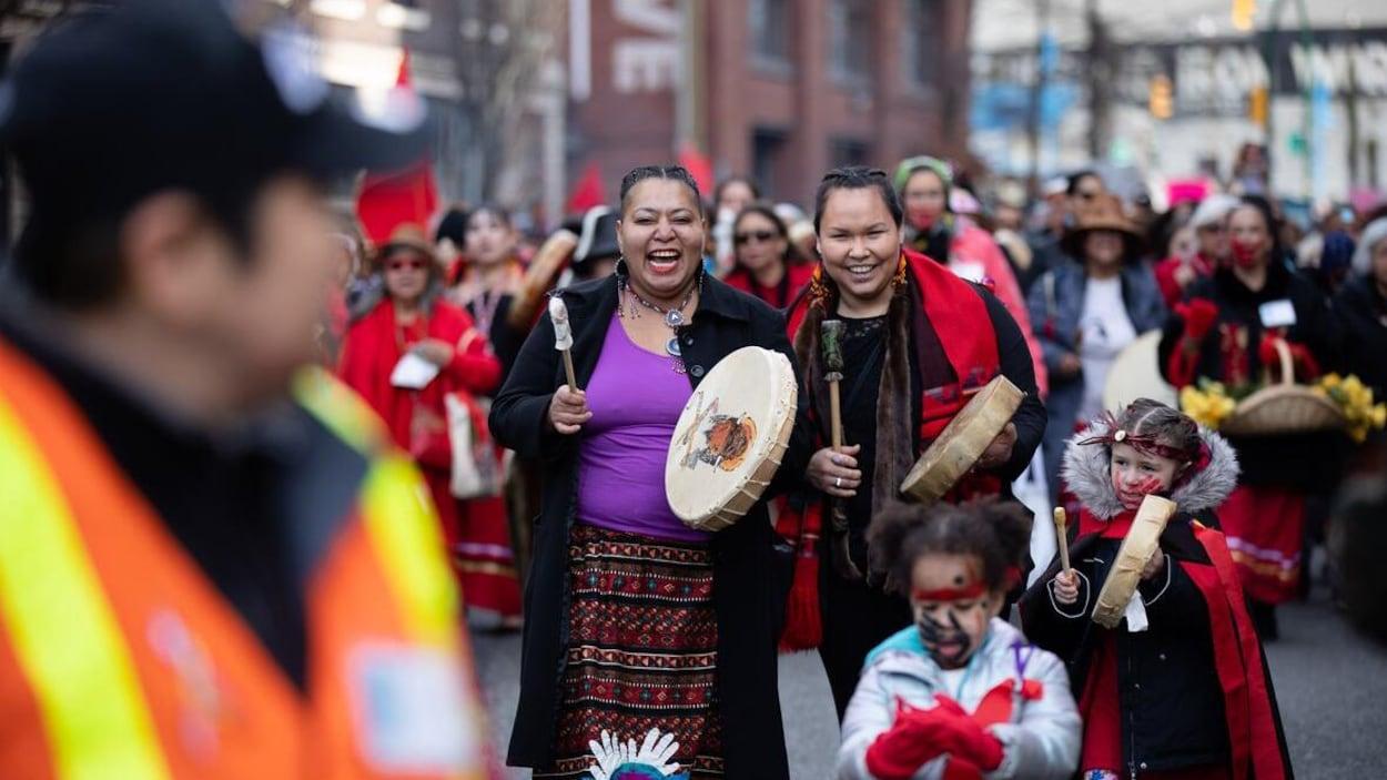 Deux manifestantes rient en tenant des tambours dans leurs mains., devant elles deux jeunes files et derrière elles, des dizaines d'autres manifestantes.