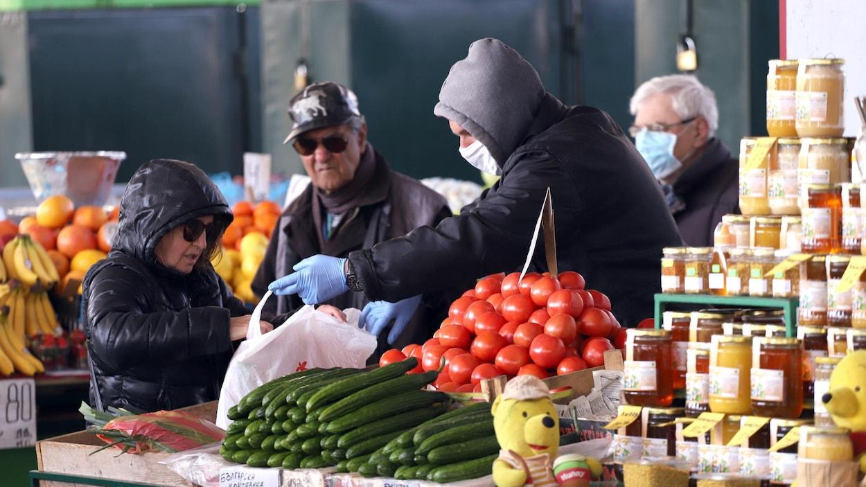 Une dame achète des légumes.