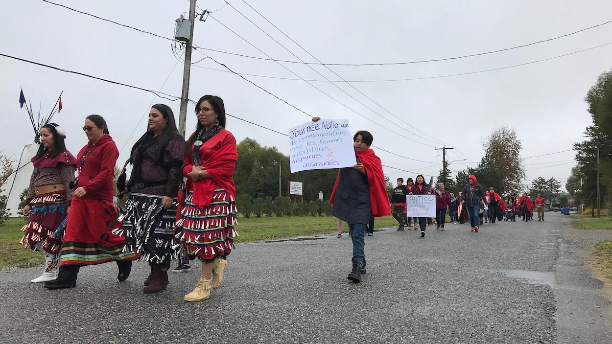 Des femmes et des hommes vêtus de rouge marchent en mémoire des femmes autochtones disparues ou assassinées.