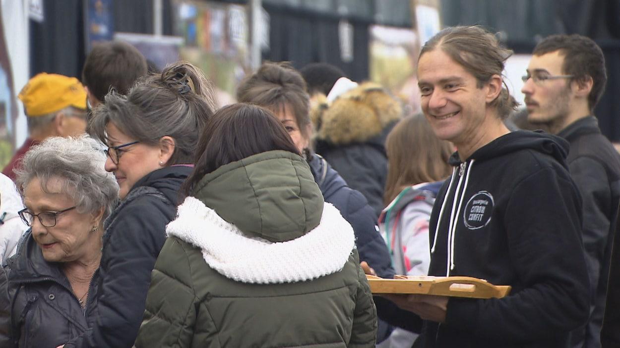 Une foule et un homme sourit à des visiteuses.