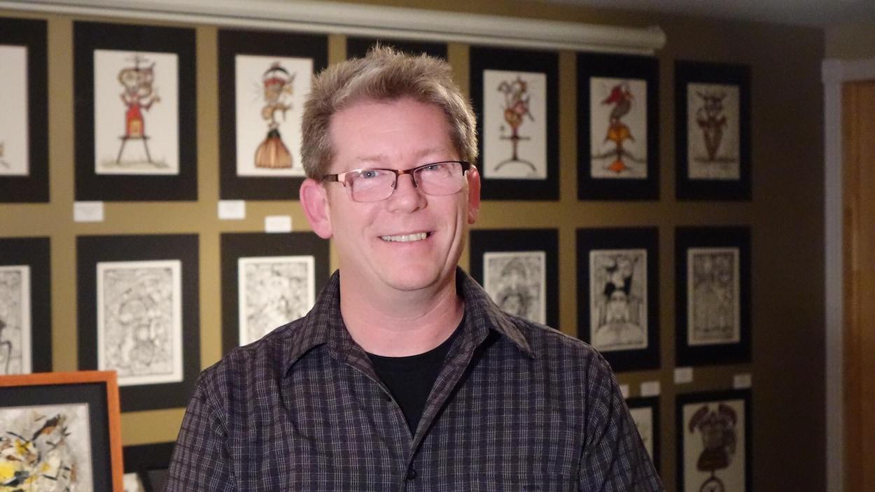 Un homme sourit à la caméra devant des peintures.