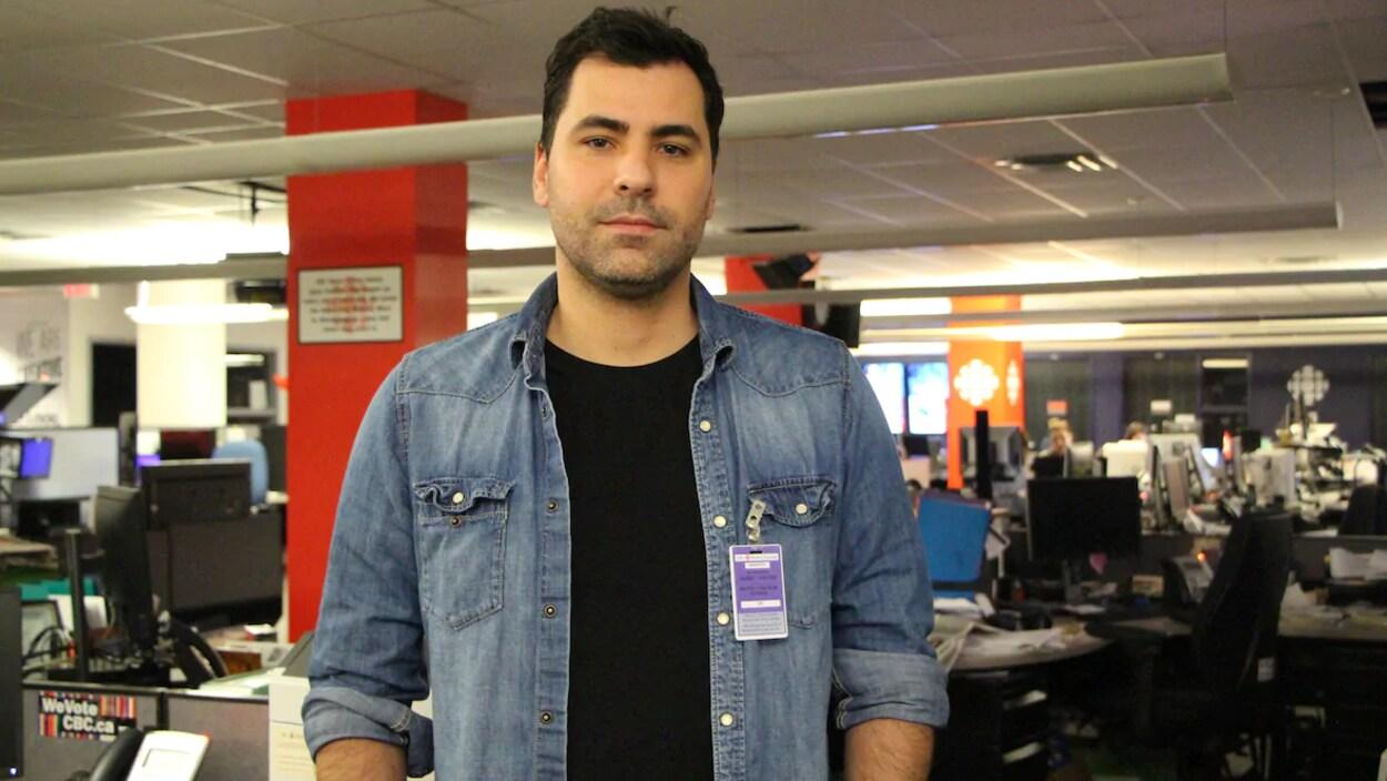 Marco Sousa pose pour la caméra dans la salle des nouvelles de Radio-Canada.