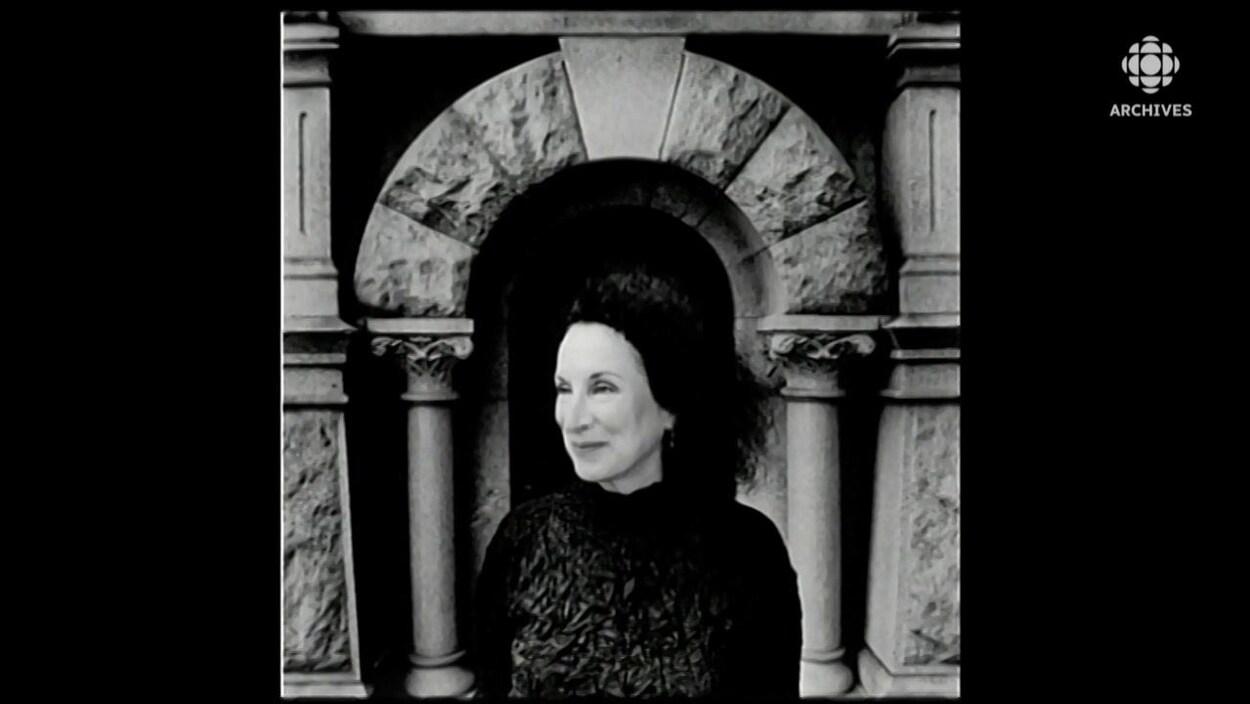 Margaret Atwood, souriante, posant devant un monument.
