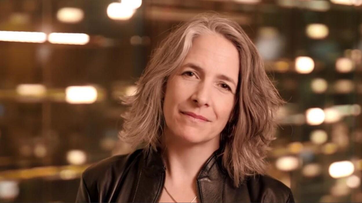 Portrait d'une femme aux cheveux gris regardant la caméra avec un fond lumineux.
