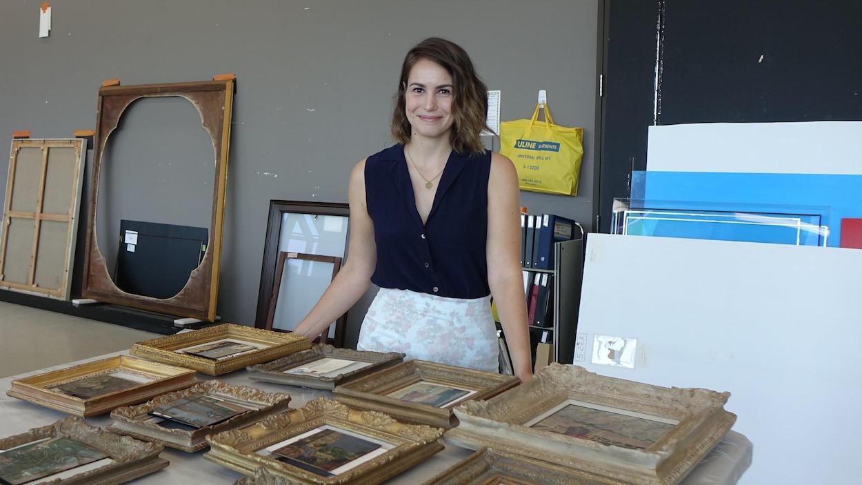 La photo montre une jeune femme dans un atelier, prenant la pose devant une table sur laquelle sont posés des oeuvres encadrées.