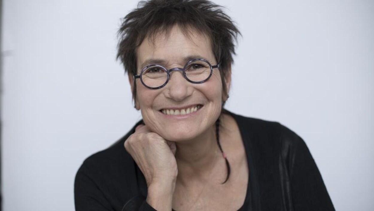 Portrait en couleur de l'autrice Marie Clark, sur fond pâle uni. Elle porte un chandail noir et des lunettes rondes, sourit et appuie son menton sur son poing droit.