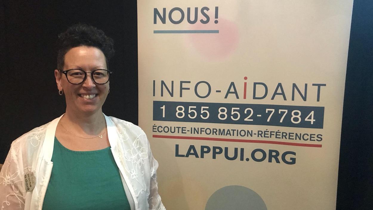 Une femme pose devant une affiche d'Info-Aidant, une ligne téléphonique.