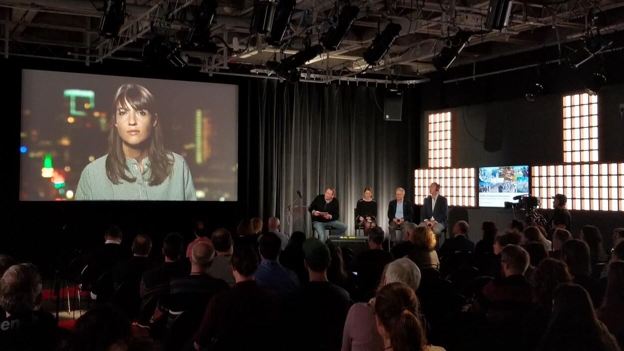 L'image d'une femme est retransmise sur écran géant à une assemblée réunie dans un studio de Radio-Canada pour une conférence.