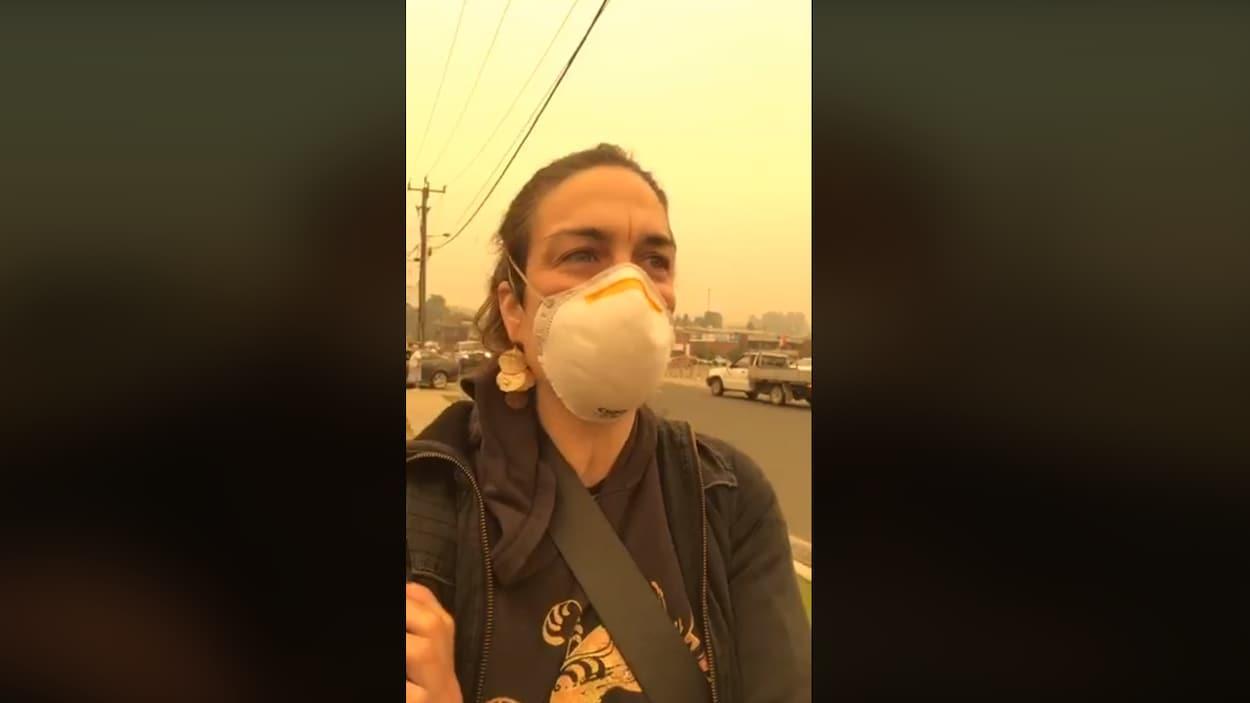 Une femme avec un masque alors que les particules de fumée de feux de forêt sont très visibles autour d'elle.