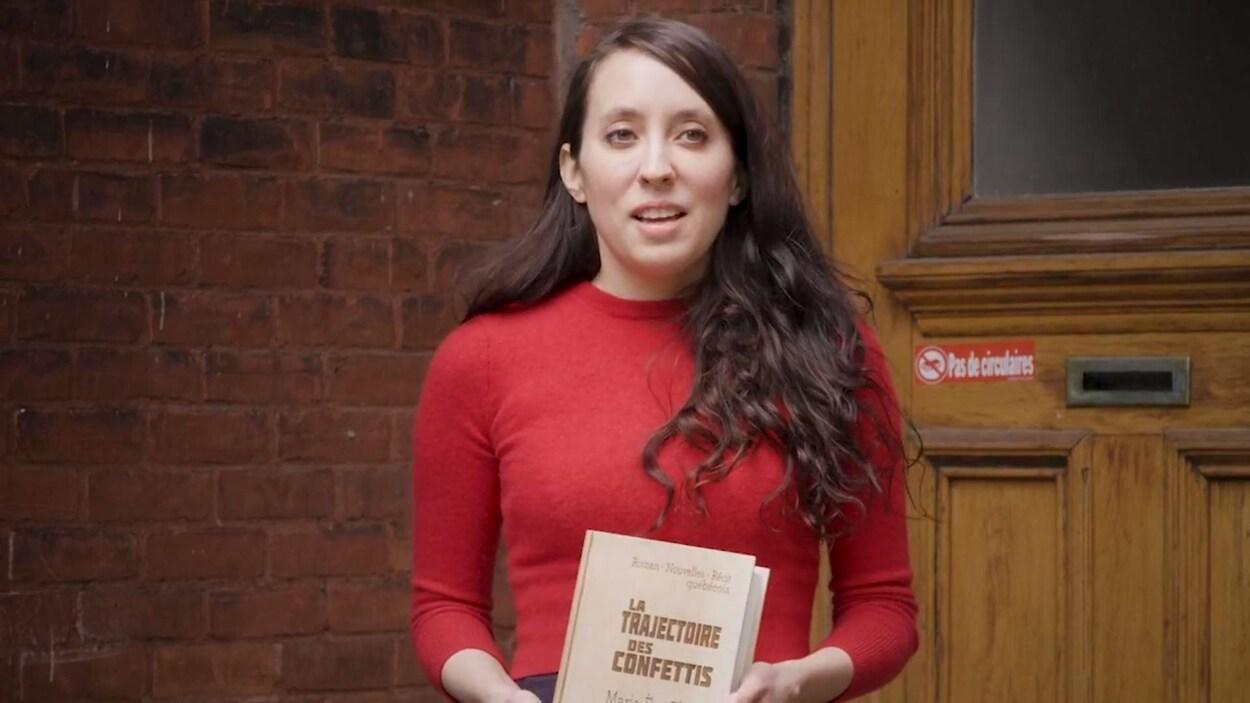 L'autrice tient son livre devant la porte de son appartement.