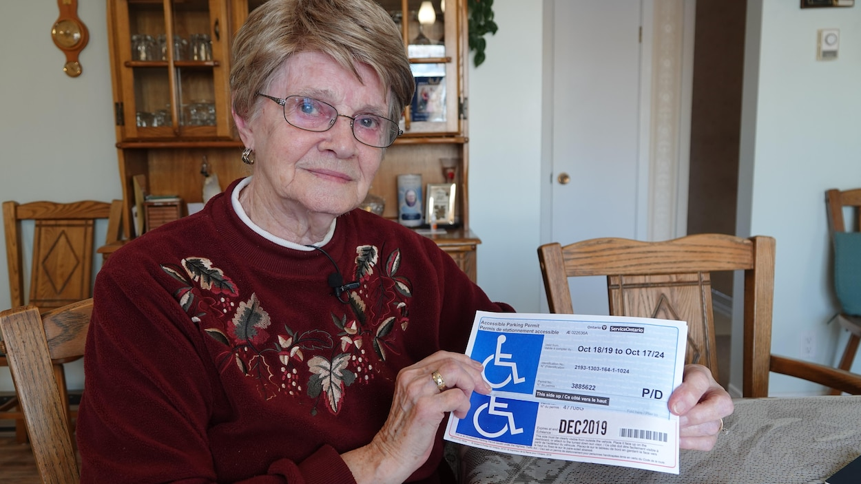 Une octogénaire tient dans ses mains son ancien et son nouveau permis de stationnement accessible.